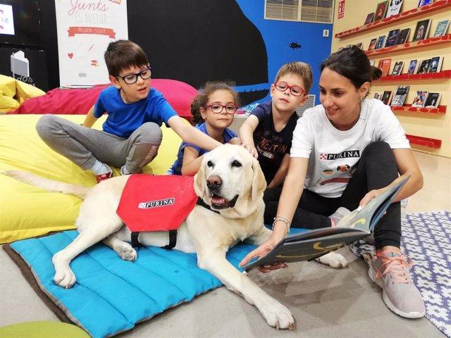 Un taller con perros de educación asistida fomenta la lectura en cien niños en la Feria del Libro de Madrid