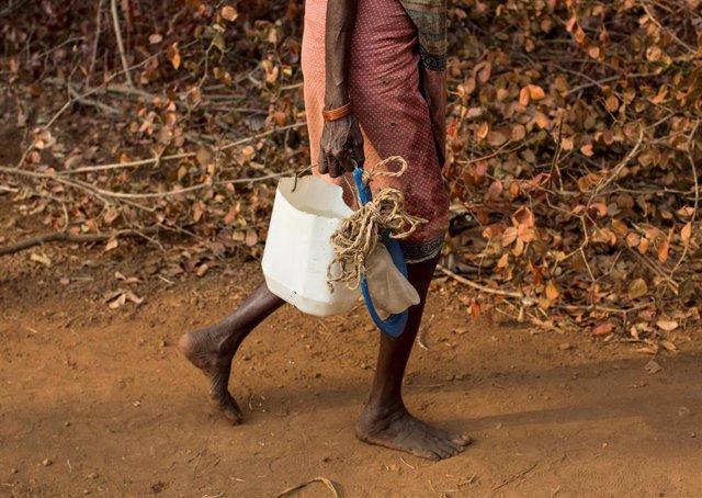 Una mujer transporta agua en una zona rural de India