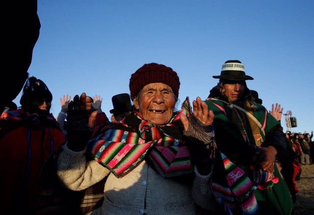 An Aymara woman raises her hands during a winter solstice ceremony that coincides with the Aymara Indian New Year in Tiwanaku