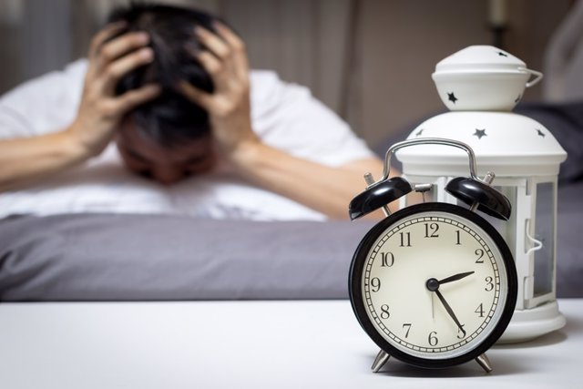 Asian man in bed suffering insomnia and sleep disorder
