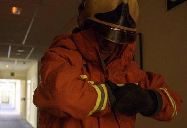 Imagen de archivo de un bombero poniéndose los guantes