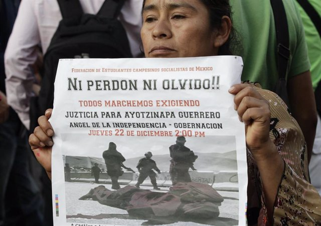A woman from a civil organization holds a poster as she takes part in a protest demanding justice for the death of two students in Ayotzinapa, during a march on streets in Mexico City