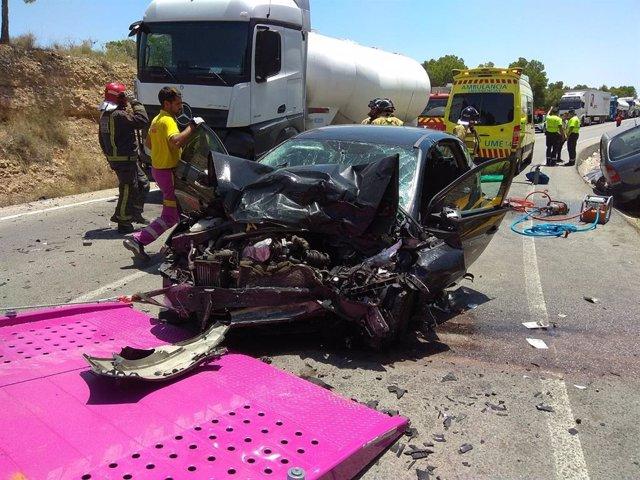 Imagen del turismo accidentado y el camión, al fondo