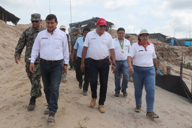 Peruvian ministers walk during a military operation to destroy illegal machinery and equipment used by wildcat miners in Madre de Dios