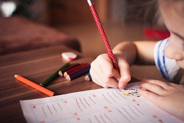Niña pintando, dibujando, haciendo los deberes