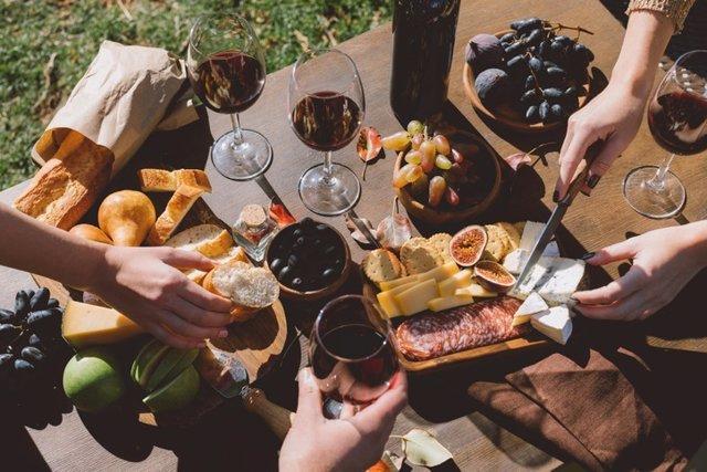 Gente comiendo y bebiendo: higos, queso curado, salchichón y vino tinto