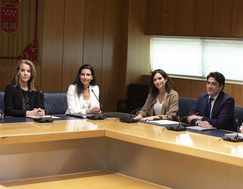 Las candidatas de Vox y PP, Rocío Monasterio e Isabel Díaz Ayuso, participan en una reunión acompañados de miembros de sus respectivos equipos.