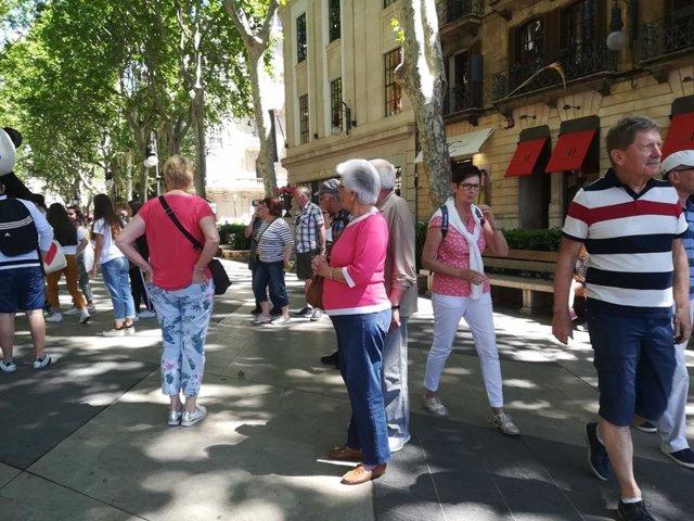 Turistas pasean por el Passeig del Born de Palma