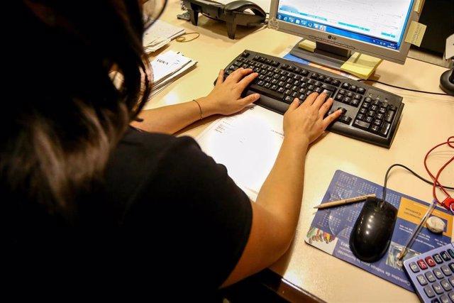 Una mujer escribe en el teclado de su ordenador, en el despacho de la oficina.