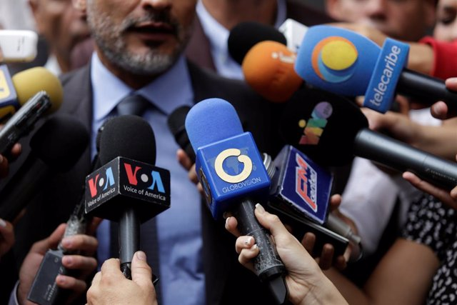 The logo of Globovision TV channel is seen on a microphone used by a TV journalist among other microphones during a news conference in Caracas