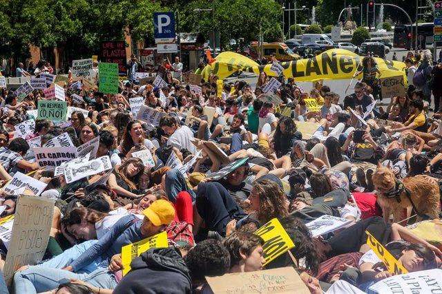 Los manifestante de la protesta en Madrid del movimiento 'Fridays for Future' contra el cambio climático se tumban en las inmediaciones del Congreso de los Diputados y la Plaza de Neptuno.