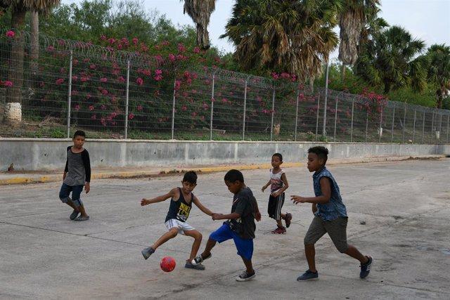 Niños migrantes juegan al fútbol en la localidad mexicana de Matamoros