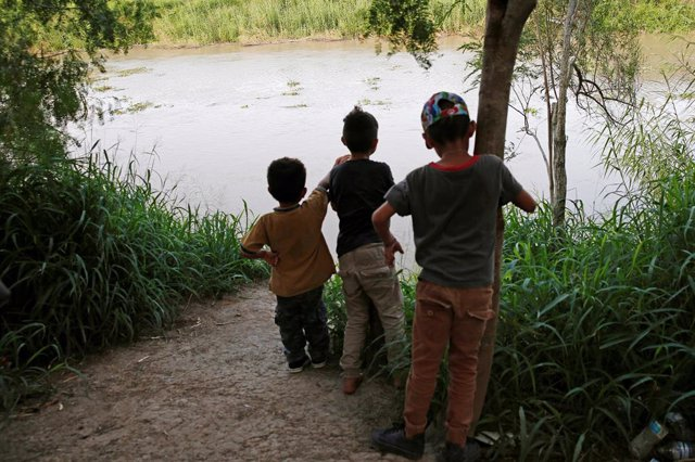Niños centroamericanos a orillas del río Grande en la frontera entre México y Estados Unidos