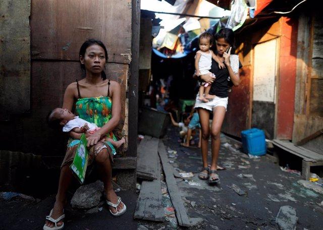 Mujeres y niños en un 'slum' de Manila