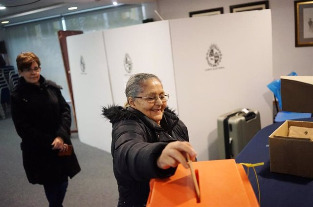 Una mujer deposita su voto en una urna durante las primarias en Montevideo.