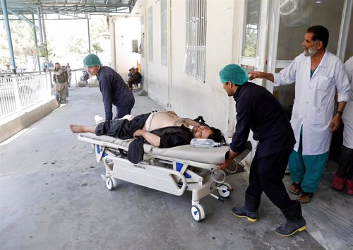 People transport an injured man to a hospital after a blast in Kabul