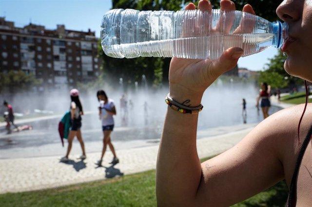 Una mujer bebe agua en una botella para refrescarse en las inmediaciones de los chorros de Madrid Río un día antes de que, según la Agencia Estatal de Meteorología (AEMET), llegue a la península Ibérica y a las Islas Baleares la primera ola de calor del v