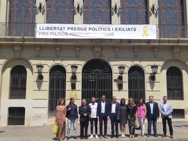 L'alcalde Miquel Pueyo amb part dels regidors de govern d'ERC, el Comú i JxCat sota la pancarta de l'Ajuntament de Lleida