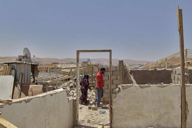 Refugiados sirios inspeccionan sus casas demolids en el este de Líbano