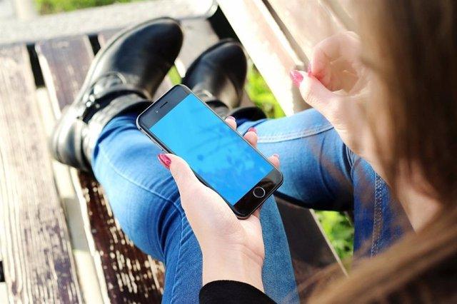 Una joven utiliza un smartphone. Recurso pantallas, móviles