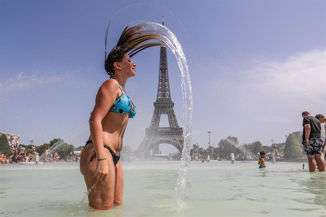 28 June 2019, France, Paris: A woman enjoys the water at the Trocadero Fountain in front of the Eiffel Tower during a heat wave. Photo: Vanessa Carvalho/ZUMA Wire/dpa