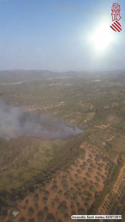 Bomberos y efectivos aéreos trabajan en la extinción de un incendio en una zona de vegetación de Sant Mateu