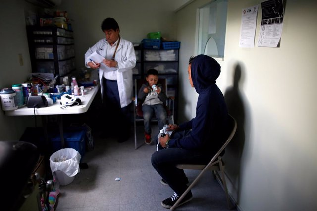 """A Central American man and child visit the doctor at the Catholic shelter """"San Francisco Javier Church\"""
