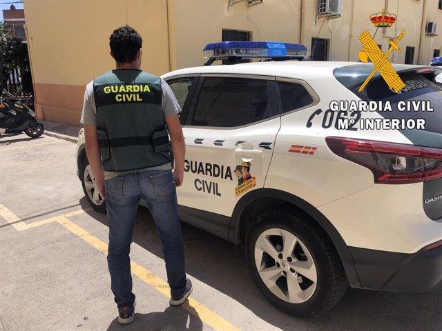 Un agentes de Guardia Civil junto a un coche en Roquetas de Mar (Almería)