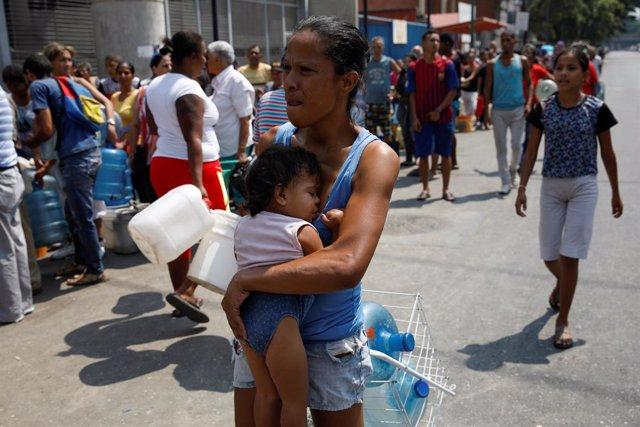 Mujer en busca de agua en Caracas