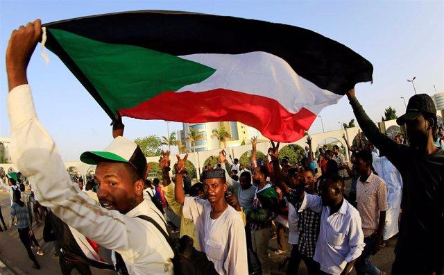 Manifestantes con la bandera de Sudán frente al Ministerio de Defensa