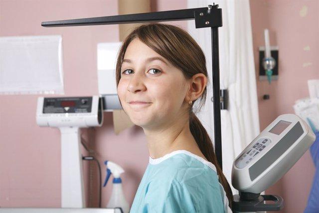 Adolescente siendo medida en el pediatra