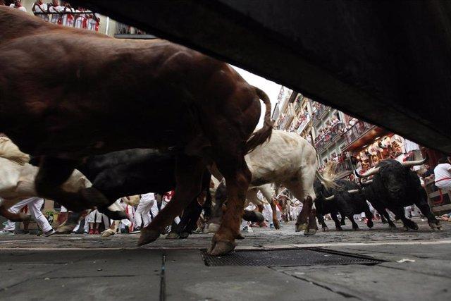 Decenas de personas corren delante de los toros en el primer encierro de las fiestas de San Fermín en Pamplona (Navarra).