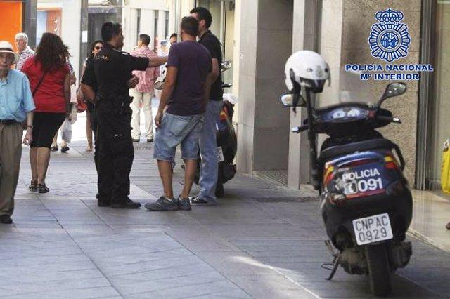 Un policía atiende a unos ciudadanos en una calle este verano