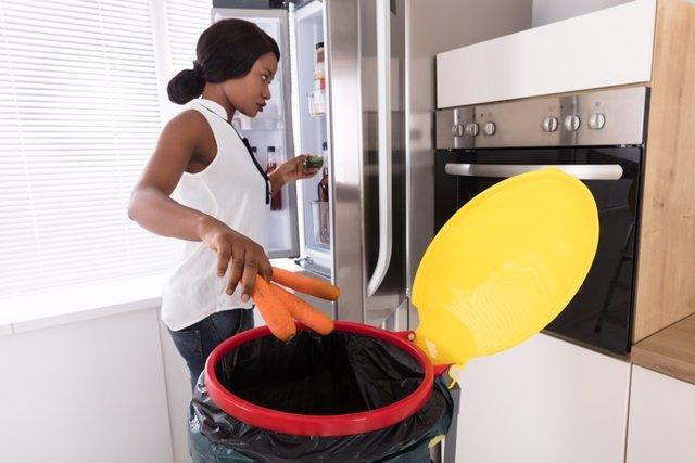 Mujer tirando zanahorias a la basura.