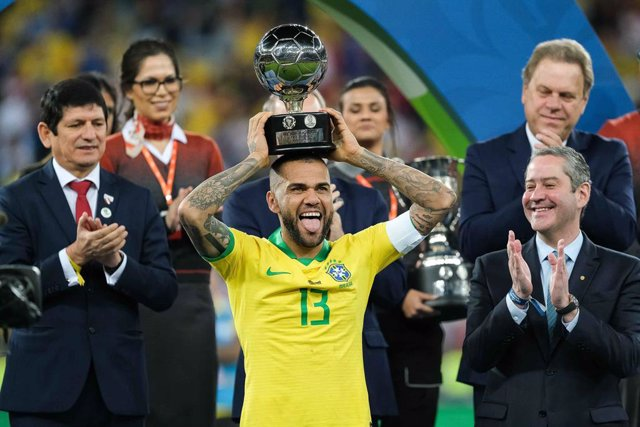 07 July 2019, Brazil, Rio De Janeiro: Brazil's Dani Alves (C) celebrates winning best player of the 2019 Copa America, after the final soccer match between Brazil and Peru at Maracana Stadium. Photo: Diego MaranhᎣo/AM Press via ZUMA Wire/dpa