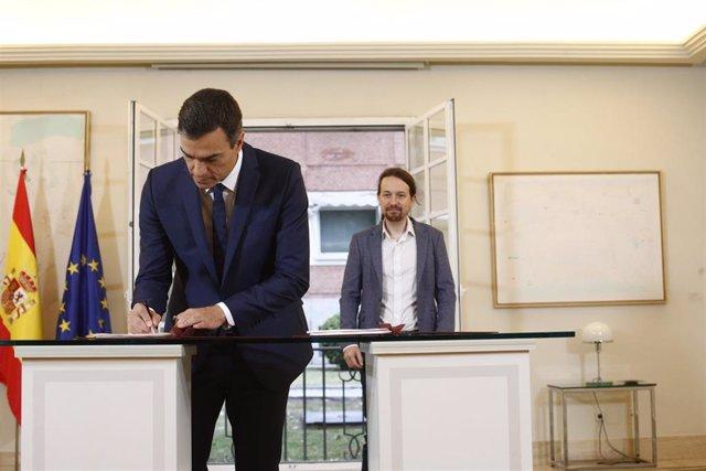 El presidente del Gobierno, Pedro Sánchez, firma con el secretario general de Podemos, Pablo Iglesias, su acuerdo para los presupuestos en la Moncloa