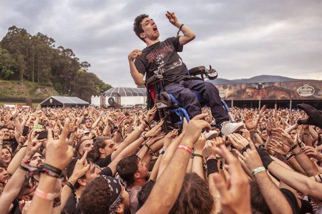 Un joven en silla de ruedas es levantado en el aire por el público durante el'Re