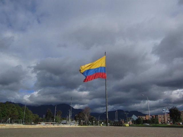 La bandera de Colombia ondea en una plaza.