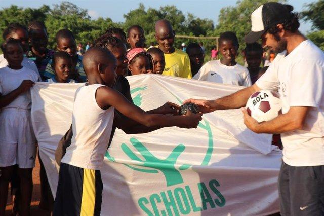 Niños de Chicomo, Mozambique, en 2018, haciendo entrega de la pelota artesanal al equIpo de Scholas Deporte, para que esta fuera bendecido por el Papa Francisco