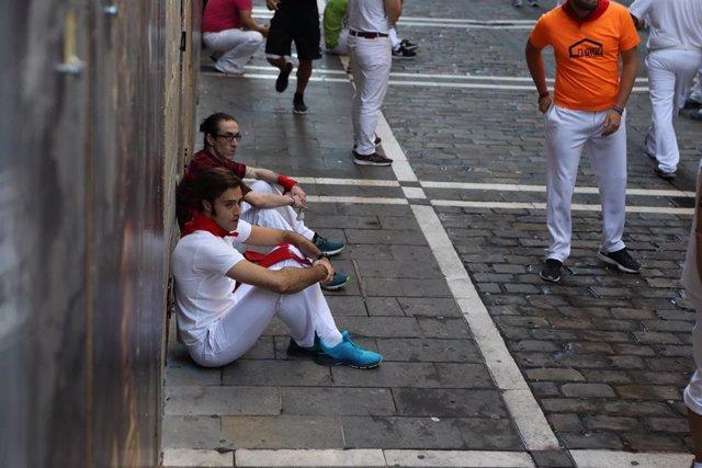 Corredores sentados antes del quinto encierro de los Sanfermines de 2019, con toros de Victoriano del Río.