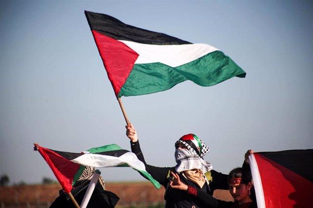 Una manifestante con una bandera palestina