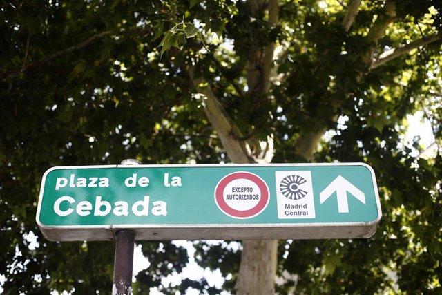 Señal de dirección de la Plaza de la Cebada con símbolo de prohibido aparcar al lado del distintivo de Madrid Central.