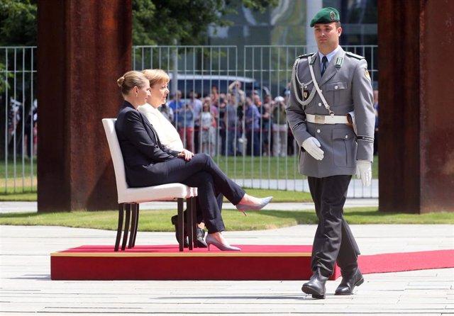 Angela Merkel y la primera ministra danesa, Mette Frederiksen, pasan revista a la guardia de honor