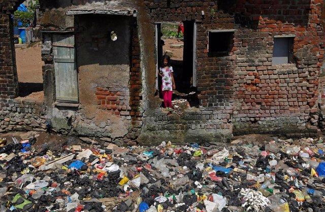 Una niña en una casa medio derruida en un slum de Bombay