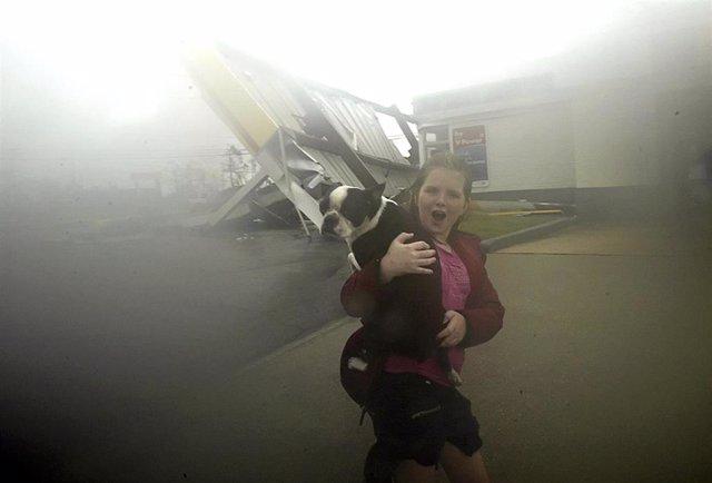 Niña de Nueva Orleans corre de la lluvia con su perro en brazos