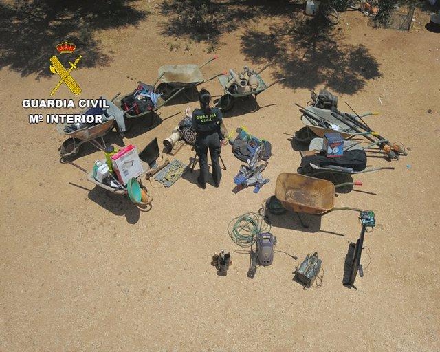 Una agente con parte de los objetos sustraídos ya recuperados en una finca de Fuente Palmera (Córdoba).