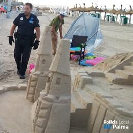 Agentes de la Policía Local de Palma, durante el operativo en el que han retirado castillos de arena de la playa de Palma.