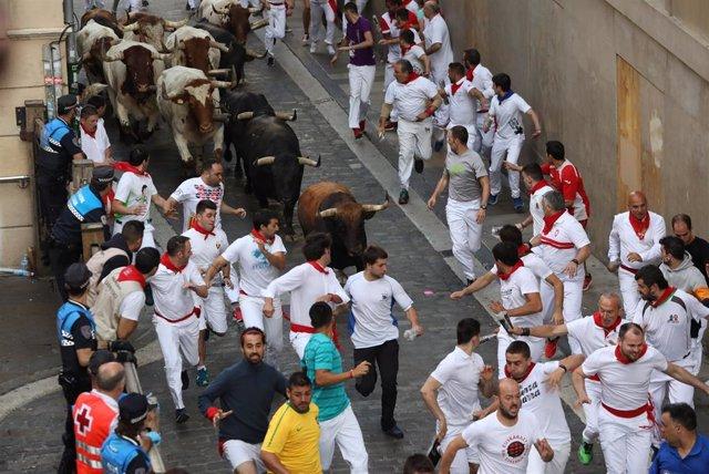 Cientos de personas corren delante de los toros de La Palmosilla en el séptimo encierro de las fiestas de San Fermín celebrado en Pamplona (Navarra).