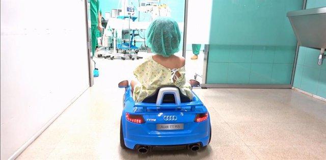 Un niño llegando al quirófano con el vehículo eléctrico
