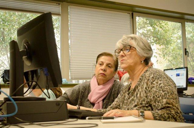 Dos mujeres de la tercera edad mirando la pantalla de un ordenador